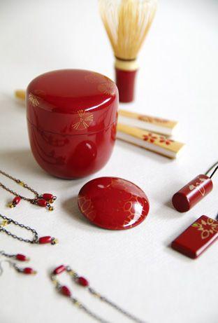 (上から)茶箱用の小振りな茶筅、扇子、朱漆地に金蒔絵の棗とブローチ、朱塗漆絵ペンダント、朱塗ビーズのネックレス…