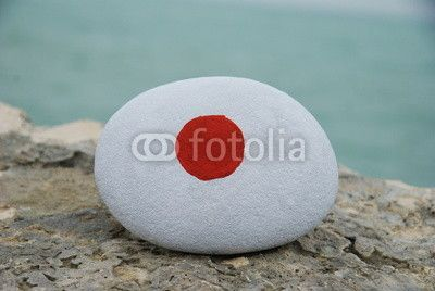 Flag of Japan on a stone with sea background