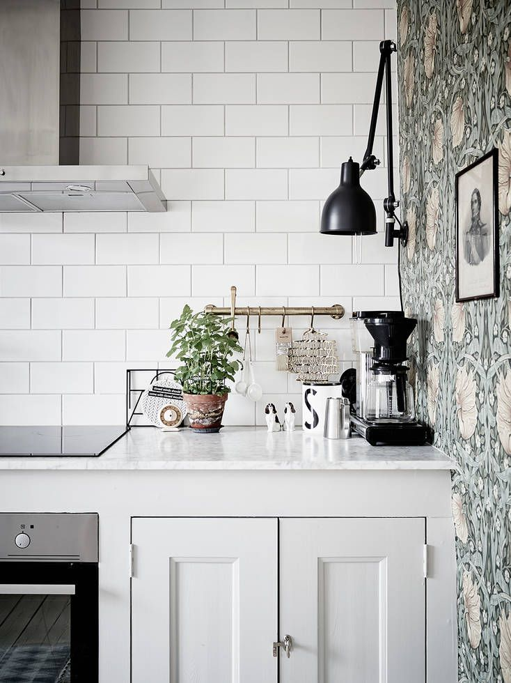 Kitchen corner where subway tiles meet antique wallpaper in a home in Göteborg, Sweden. Ceramic and cut metal art help blend the two styles together.