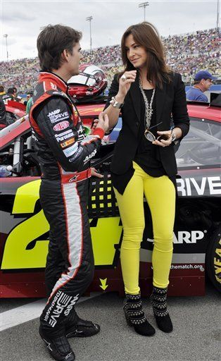 Jeff Gordon, left, and his wife, Ingrid Vandebosch, wait on the grid before Sunday's NASCAR Sprint Cup Series auto race, March 25, 2012, in Fontana, Calif.