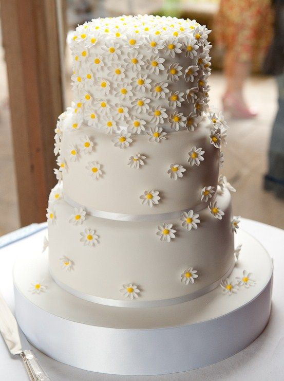 Tumbling daisy wedding cake that would fit well with a country garden theme. Check out the website for more