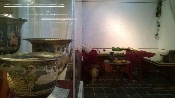 Vetrina con selezione di crateri apuli a figure rosse, recuperati dal Gruppo Tutela Beni Culturali della Guardia di Finanza di Roma. Sullo sfondo ricostruzione di un triclino (sala per il banchetto)