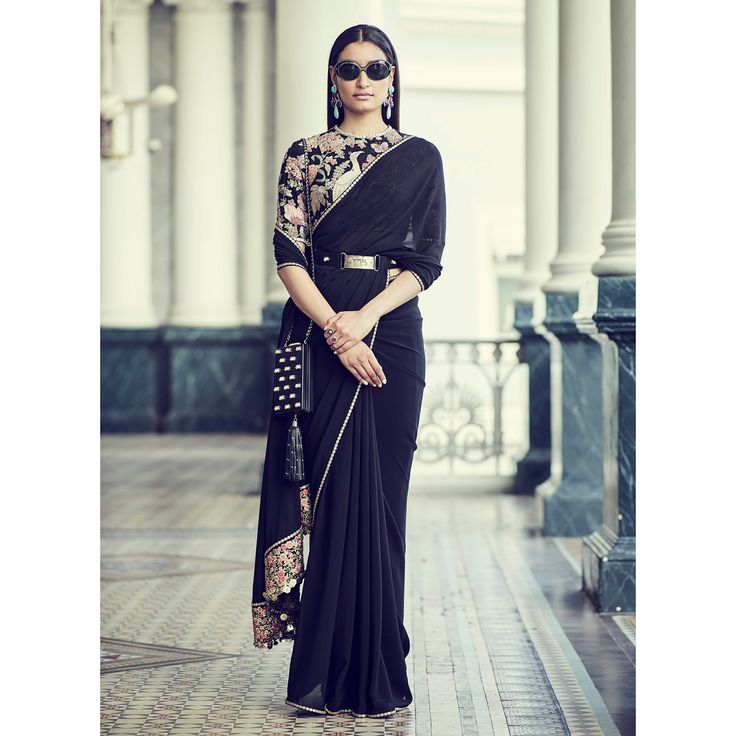 Romantic power dressing in a jet black saree. The lavish blouse is hand-embroidered on black tulle with vintage threadwork and appliqué, mimicking an eighteenth century Parisian tapestry featuring European flora and fauna. The black silk georgette saree is edged with a tiny hand-embroidered border and a floral embroidered pallu fringed with metallic sequins. The whimsy is juxtaposed with our new Bengal tiger military belt in black leather and our 1920s industrial box clutch detailed with…