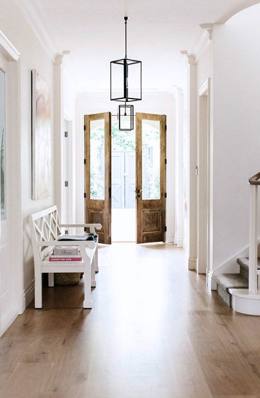 Stunning entryway with vintage double doors, hardwood floors, white walls, a white bench and oversized art on the walls | Photographs for est magazine