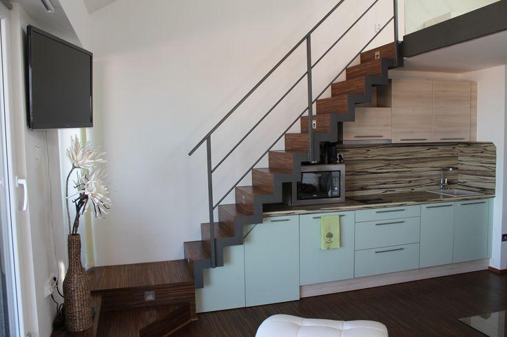 Moderní kuchyně a osvětlené schodiště.
