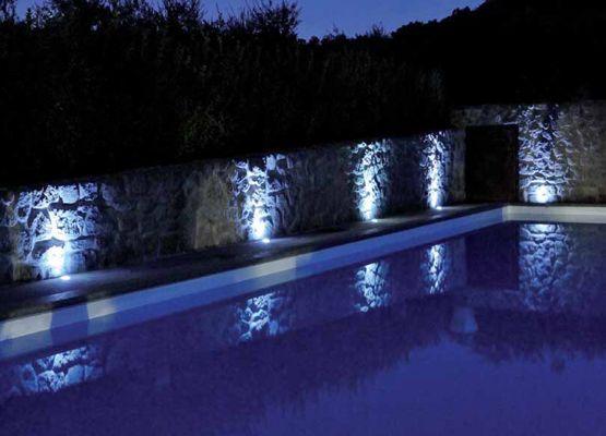 un bordo piscina illuminato con faretti led bianchi