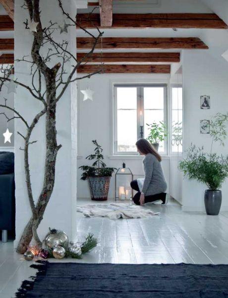 Signe har pyntet op med et par store nøgne grene med stjerneformede spejle på. På gulvet ligger sølvkugler i forskellige størrelser på en grangren – tilsammen giver det en fornemmelse af sne og is. Gulvtæppet er fra Private 0204. Lanternen og det lille træ i baggrunden er begge fra I Rosens Navn. TIP: Bring naturen indenfor ved at indrette med skind, blomster, grene og gran. Sæt lanterner og lys til, og der er julehyggelig stemning.