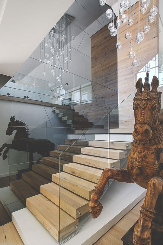 Glass staircase with wooden steps, flanked by two antique carved horses, unique hanging crystal glass bulbs light fixtures.