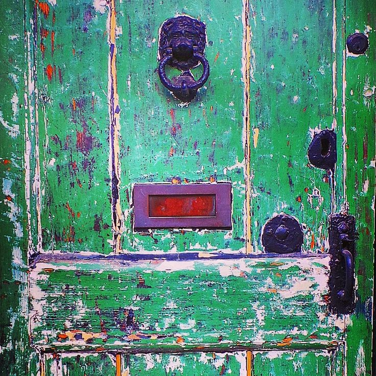 Close up of an aged green door on a house in Fletching..