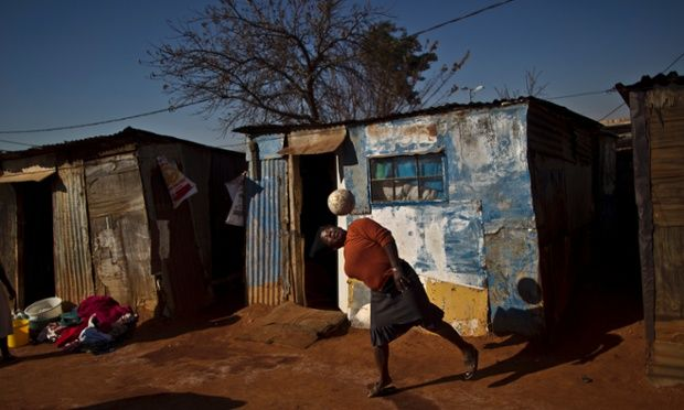 A South African woman plays football next to her homes in a Soweto, South Africa