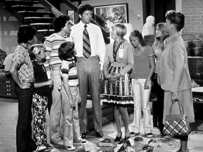 In this scene from an early episode of 'The Brady Bunch,' Christopher Knight, left, Susan Olsen, Barry Williams, Mike Lookinland, Robert Reed, Florence Henderson, Eve Plumb, and Maureen McCormick are joined by Ann B. Davis.