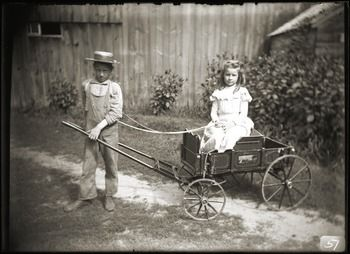 Boy pulling girl in a toy wagon (Greenwich, Mass.), ca. 1910