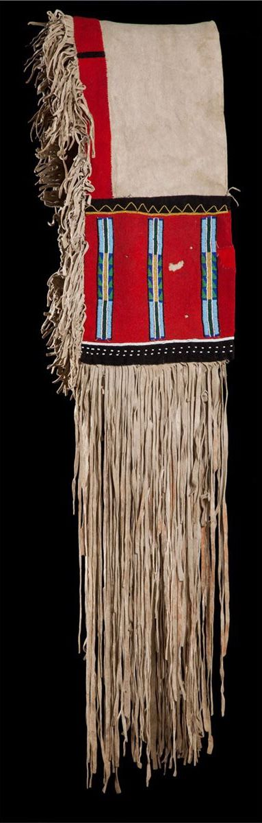 """Blackfoot Saddle Bags. ДА1. Pair of drape saddlebags or serapes with long 32"""" fringe, red trade cloth field with multicolored beading in geometric patterns. Black wool edging and accents. Fringed edge across the entire back. Green pigment. They hang at 54"""" making them 108 inches from the end of the fringe spread flat by 11"""" wide. The fringe is 32"""". Brian Lebel's High Noon Auction, Jun. 2015."""
