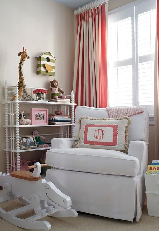 Pink and beige nursery features walls painted beige lined with a green striped birdhouse mounted on wall over a white Jenny Lind Bookcase next to a white slipcovered glider accented with a monogram pillow alongside a white dinosaur rocker placed under window dressed in white and pink vertical stripe curtains.