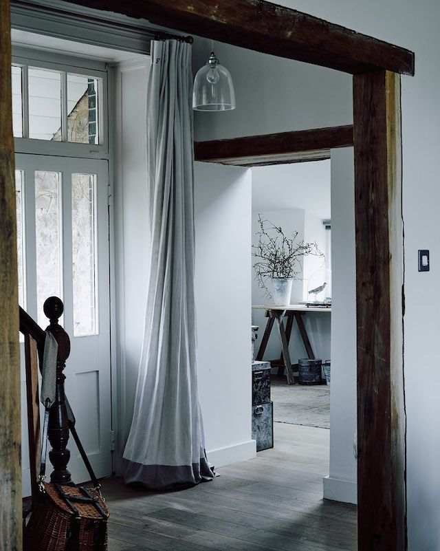 Linen curtain to keep out the draft in the hallway of the cosy winter home of  photographer Michael Sinclair.