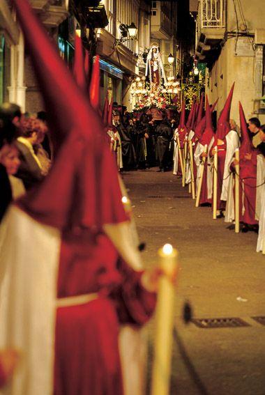 Una foto de una procesión de Semana Santa. Vemos los trajes religiosas y cientos de residentes que vienen a mirar a la procesión. Las procesiones empiezan en el domingo de ramos y terminan en el Pascua.