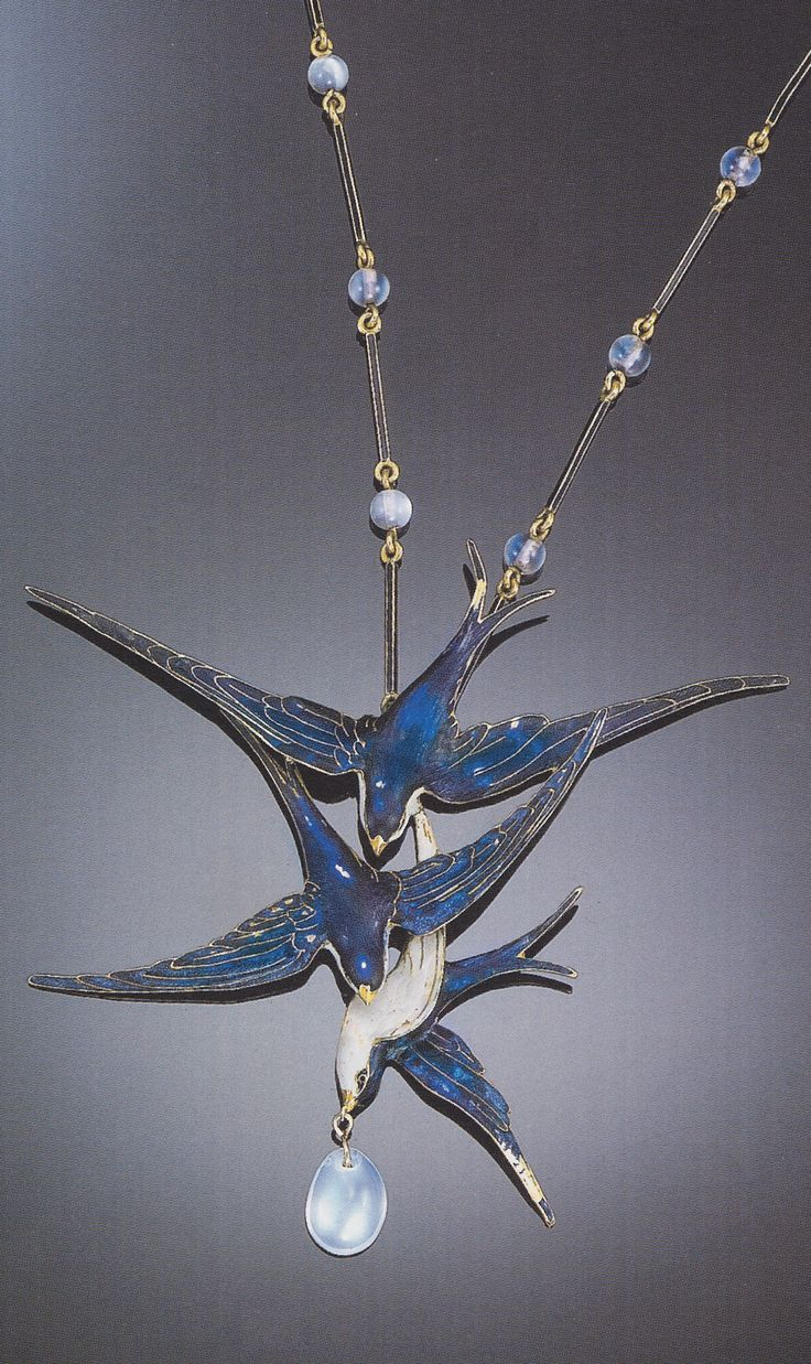 LUCIEN GAILLARD - AN ART NOUVEAU ENAMEL AND MOONSTONE NECKLACE. The pendant necklace designed as triad of diving birds embellished by varied blue enamels accented by a moonstone bead drop, suspending by a fancy link chain of black enamel bar links alternating with moonstone beads, mounted in 18K yellow gold, signed L. Gaillard. Source: Christie's catalogue, Sale 9400, Important Jewelry, 29 March 2000, Los Angeles.