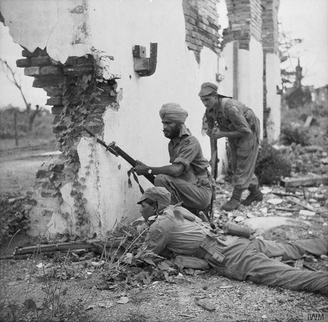 Indian soldiers of the British 20th Indian Division take cover behind a badly damaged building while looking for Japanese soldiers in Prome (Pyay), Burma. May 3, 1945