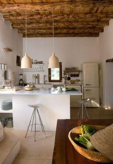 Cette cuisine vintage espagnole s'ouvre sur le salon, tout en gardant ses caractéristiques typiques et anciennes : électro-ménager des années 70, niches d'origine, plafond en lambris de bois et poutres, … Et comme dans toutes les cuisines avec bar, on profite du comptoir pour préparer le dîner en sirotant son apéro avec ses amis.