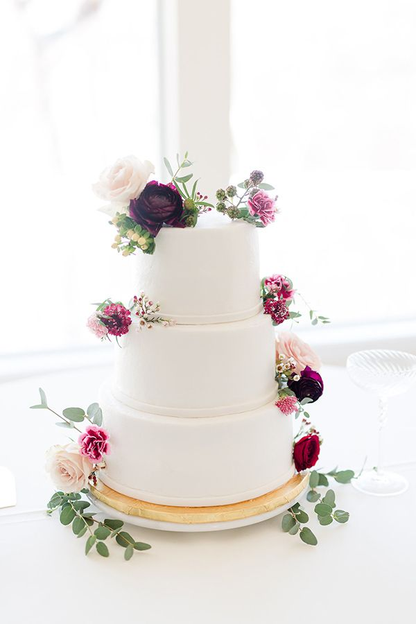 white smooth tiered wedding cake with pink flowers