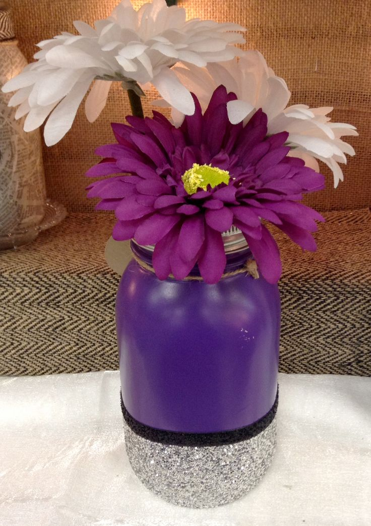 Mason jar vase/ purple spray paint/ Mod Podge, silver glitter, surface sealer/ black glitter ribbon/ regular mouth frog lid insert/ purple and white silk daisies