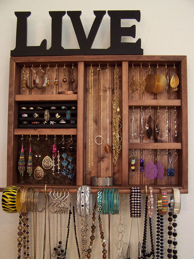 This space saving jewelry organizer will make a great addition to your small space. The jewelry organizer is stained with a custom cherry stain and it features 49 hooks to easily organize your earrings, watches, bracelets, rings, and necklaces. Includes bracelet bar, ring holder and removable dark cork board, making post earrings easy to display and access. The jewelry organizer measures: 16 inches tall 21 inches wide 2 5/8 inches deep Comes ready to hang and the mounting screws are incl...