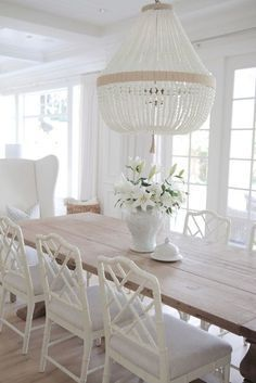 Dining room design with a neutral palette featuring a white beaded chandelier, white wood and upholstered chairs, a light wood table and pale hardwood floors - Dining Room Ideas & Decor