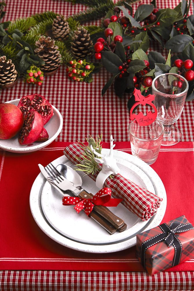 Team traditional rich red with a small-scale check for a heritage style you can update year after year. A quirky stag napkin ring, cute Christmas pudding place card and stoneware crockery add a contemporary twist. Photography: Dan Duchars. housebeautiful.co.uk