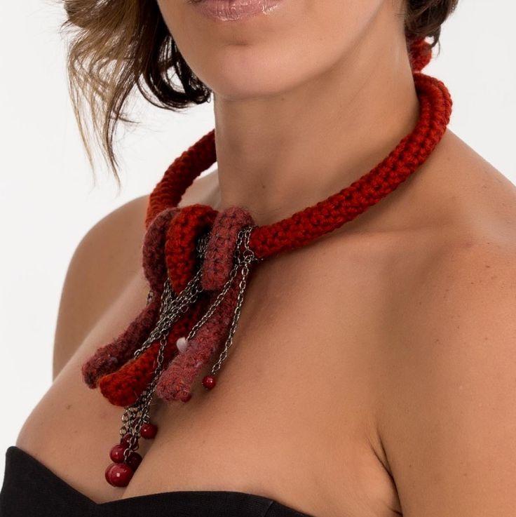 Collar elaborado artesanalmente a partir de una estructura de metal cubierta con un tubo tejido con lana roja mediante la técnica de crochet en punto bajo, en contraste con cadenas de color oro viejo y piedras de cristal rojas.