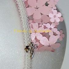 Detalle de tocado de niña en forma de corona. Flores troqueladas de color rosa en cartulina nacarada