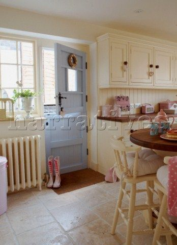 Cream sunlit country kitchen with pink accessories and pastel blue back door. I could faint...