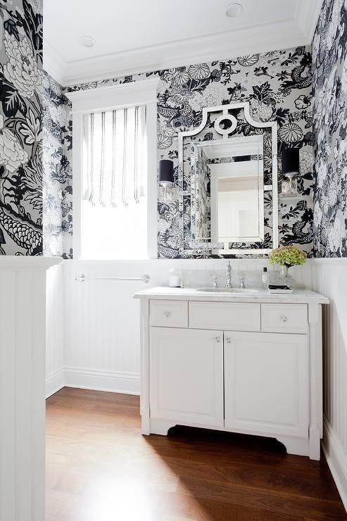 Black and silver powder room features top half of walls clad in black and silver wallpaper, Schumacher Chiang Mai Dragon Smoke, and bottom half of walls clad in white beadboard trim lined with a white washstand adorned with shiny nickel pills topped with honed white marble fitted with a hammered metal sink and vintage style faucet as well as a mirror lit by sconces accented with black shades.
