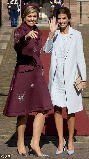Juliana Awada, wife of Argentina's President Mauricio Macri, right, and Dutch Queen Maxima wave for the cameras as they arrive at the Dutch Prime Minister's office in The Hague