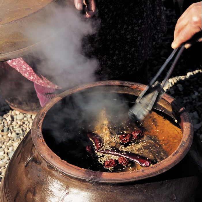 Soy sauce being prepared in a traditional urn is purified with hot charcoal.