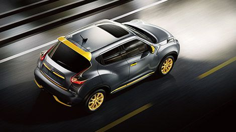 2015 Nissan Juke shown in custom design colors of black and yellow. Aerial view of Juke driving on highway