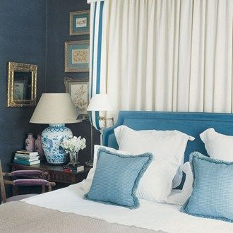 If you don't have room for a four-poster bed then a pelmet like this one by Paolo Moschino can be a creative alternative. The linen curtains are made from 'Nyvelle Oyster' by  Paolo Moschino for Nicholas Haslam. The clean, straight lines and border of blue stands out against the dark walls.  Taken from the June 2012 issue of House & Garden