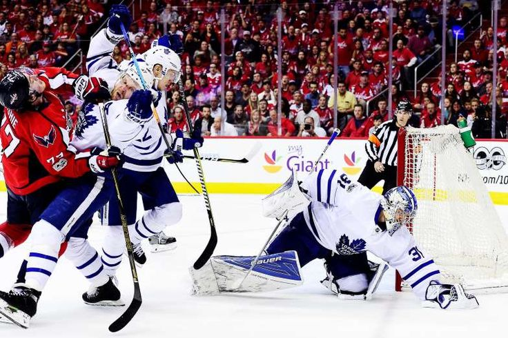 COLLISION AND A SAVE:    Frederik Andersen of the Toronto Maple Leafs makes a save as T.J. Oshie of the Washington Capitals and Leo Komarov of the Toronto Maple Leafs collide in the third period in Game Five of the Eastern Conference First Round during the 2017 NHL Stanley Cup Playoffs at Verizon Center on April 21, in Washington, DC.