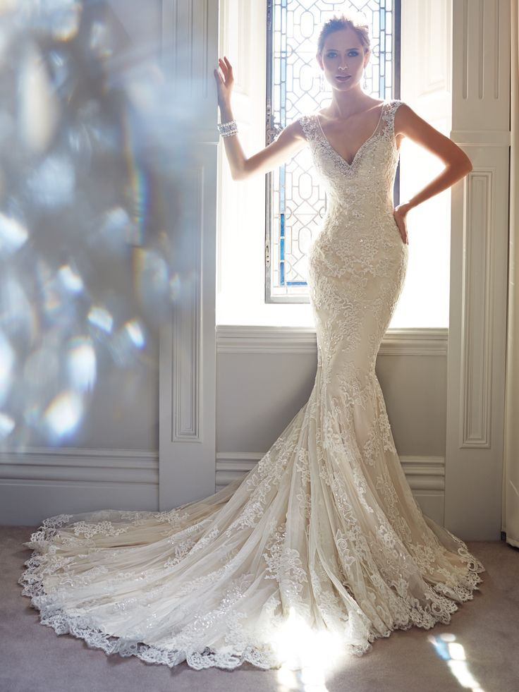 Sophia Tolli - Y21432 – Leigh -     Lace wedding dress with cap sleeves, sheath with point d'esprit and lace appliqués,plunging V-neckline framed with crystal hand-beading, crystal buttons cascade down the back concealing a zipper closureandchapel lengthtrain.  Sizes: 0 – 28      Colors: Light Gold/Ivory, Ivory, White