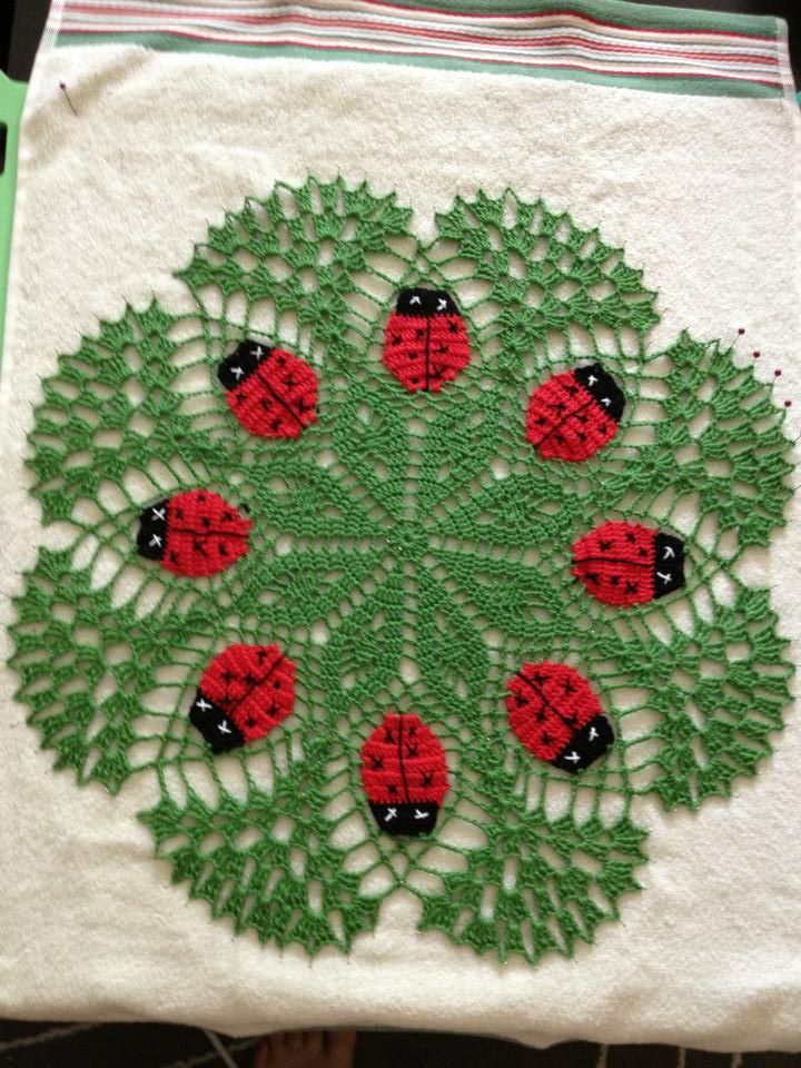 A green ladybug crochet mat, with red and black thread detailing, and intricate star pattern interwoven with delicate trellis style loops.