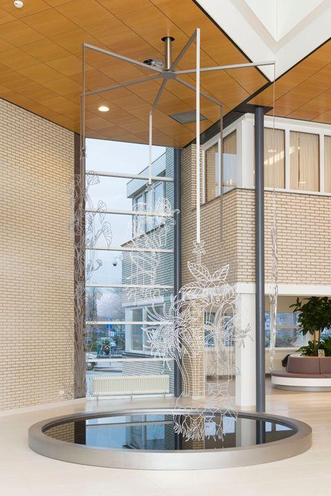 Over het kunstwerk All is Well - AllisWell - Ziekenhuis - Máxima Medisch Centrum    Het werk bestaat uit een spiegelende vijver (met een diameter van 4 meter) met zwevend daarboven zes roestvrijstalen figuren (elk ongeveer 2,5 x 1 meter). Iedere figuur verwijst naar een ander botanisch element, en alle figuren hangen boven de vijver zonder het water te raken.