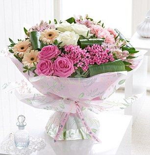 Mother's Day Majestic Hand-tied, £55, Interflora, with contrasted warm shades of pink with creamy white and pale peach