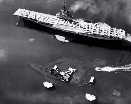 USN 1036055: USS Bennington (CVA-20). Passes the wreck of USS Arizona (BB-39) in Pearl Harbor, Hawaii, on Memorial Day, 31 May 1958. Bennington's crew is in formation on the flight deck, spelling out a tribute to the Arizona's crewmen who were lost in the 7 December 1941 Japanese attack on Pearl Harbor. Note the outline of Arizona's hull and the flow of oil from her fuel tanks. Official U.S. Navy Photograph, now in the collections of the National Archives.