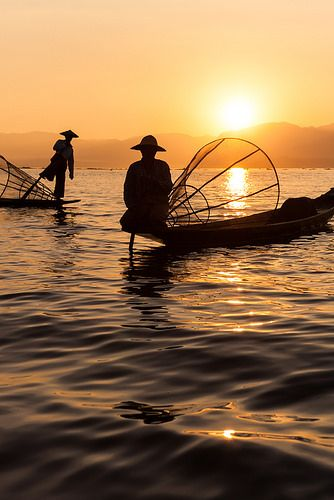 Silhouettes of fishermen at sunset on Inle lake by Marjorie Lang