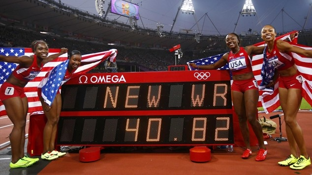 USA relay team members Tianna Madison, Carmelita Jeter, Bianca Knight and Allyson Felix pose with the scoreboard indicating their new world record time of 40.82 and victory in the women's 4x100m relay final during the 2012 London Olympic Games at Olympic Stadium. (Photo: Reuters) #NBCOlympics
