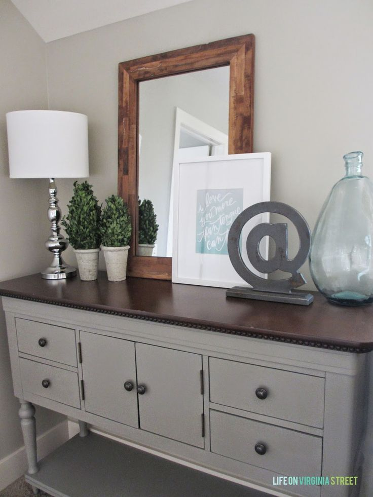 Buffet painted in Annie Sloan chalk paint in French Linen. Wall color is Behr Castle Path. Lovely vignette!