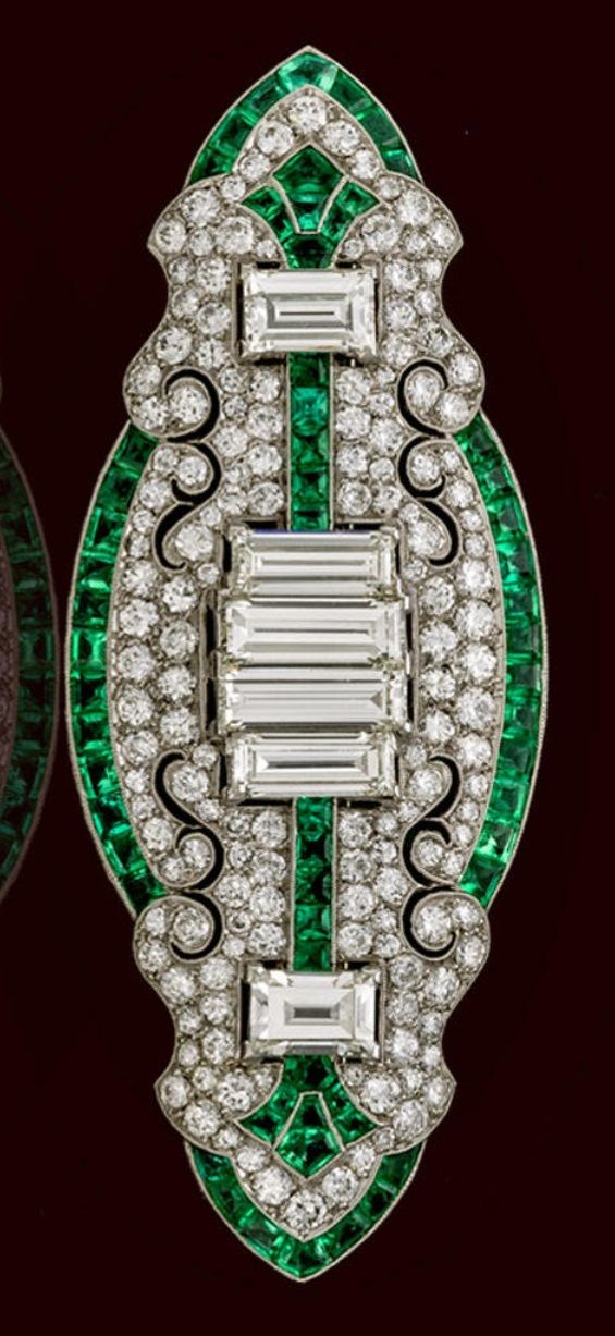 An Art Deco diamond and emerald brooch, circa 1925. Of shaped-oval outline…