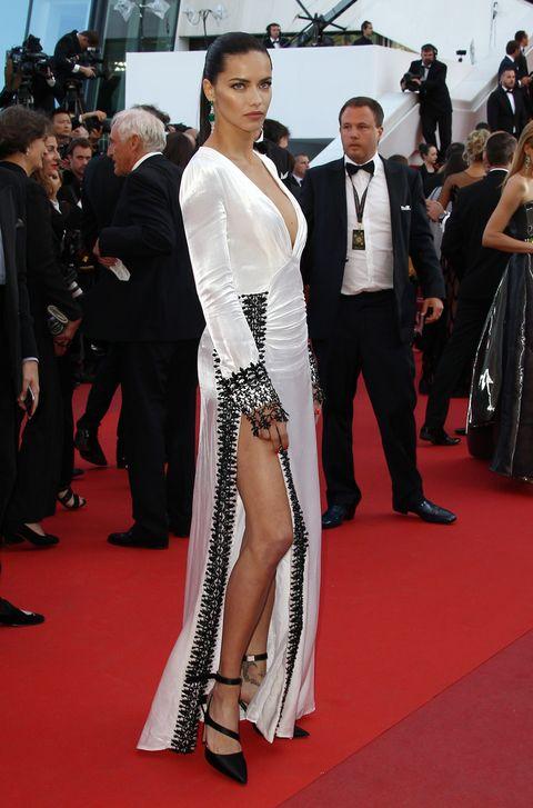 En el festival de Canne de 2016 Adriana Lima presumió de pierna y escote con este vestido 'black & white'. En los pies llevó unos salones negros atados al tobillo.