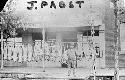 A man standing outside the shop of J. Pabst, Wholesale & Retail Butcher in Eaglehawk. There is a row of carcases suspended outside the shop. 1865