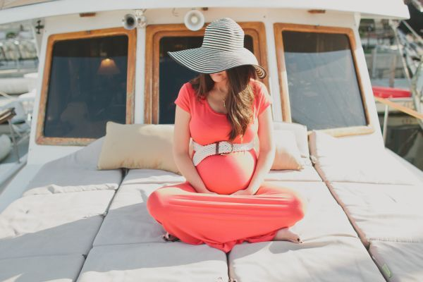 Wedding PR, Wedding Public Relations, WEdding Marketing Expert, nautical maternity session, boat, beach, sand, ocean, coral maxi dress, floppy hat, Aaron Young photography, seaside maternity session ideas, end of summer boat maternity session, boat shoes, statement necklace