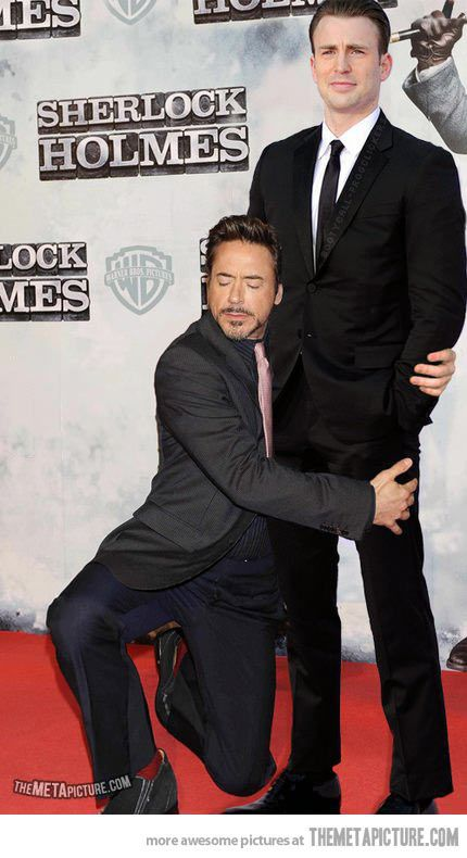 """Iron Man holding Captain America. They are so cute! RDJ looks like a content kitten, while Chris looks like the owner thinking """"WTF!?!??"""""""